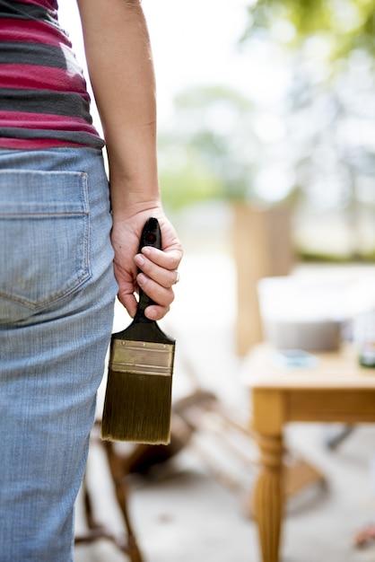 Closeup tiro de uma mulher segurando um pincel grande com um fundo desfocado Foto gratuita