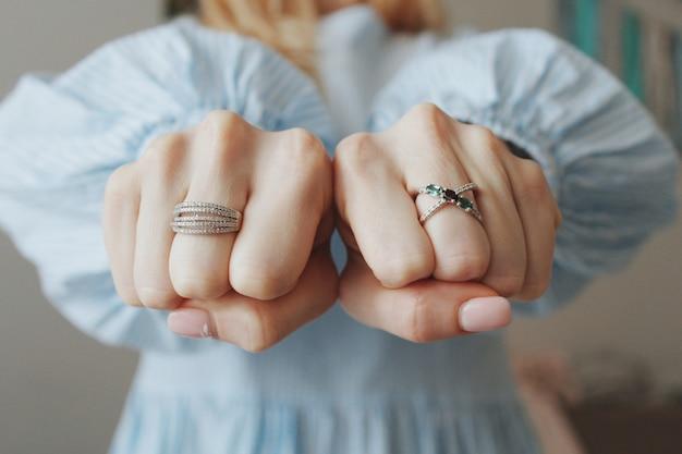 Closeup tiro de uma mulher usando lindos anéis nas duas mãos e mostrando os punhos Foto gratuita