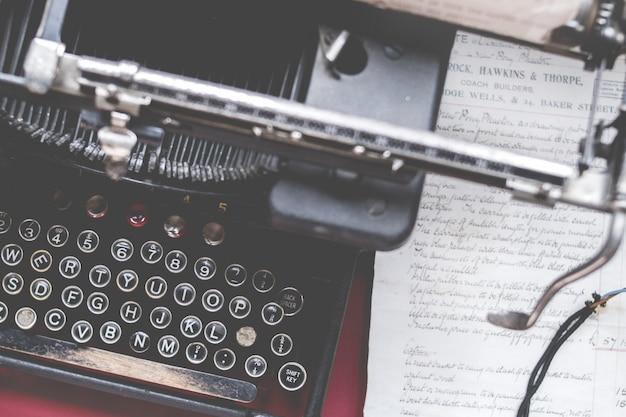 Closeup tiro de uma velha máquina de escrever vintage em uma mesa vermelha com papel ao lado Foto gratuita