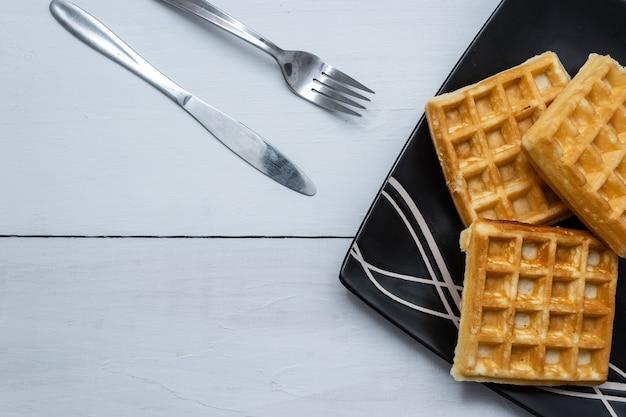 Closeup tiro de waffles quadrados em um fundo de mesa de madeira Foto gratuita