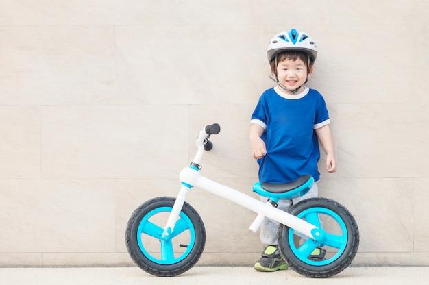 Closeup uma criança ficar no chão de pedra de mármore com bicicleta Foto Premium