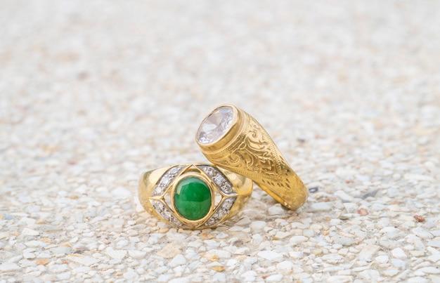 Closeup velhos anéis de diamante no fundo do chão de pedra turva Foto Premium