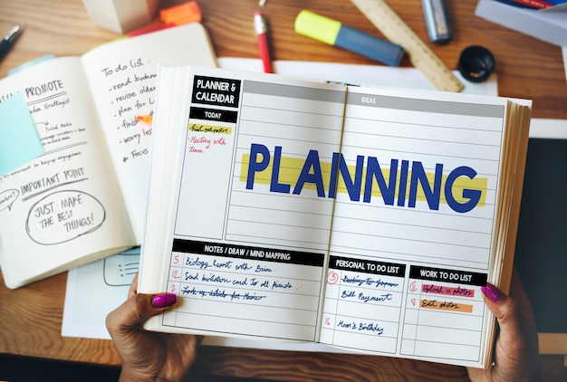 Closeup vista aérea de mãos abertas organizar o livro com a palavra de planejamento Foto gratuita