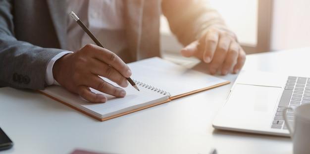 Closeup vista do jovem empresário profissional escrevendo seus conceitos de idéia no notebook Foto Premium