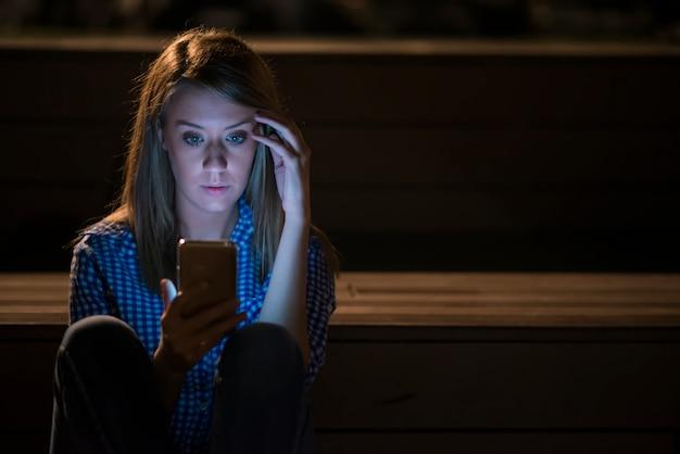 Closeup vista lateral do retrato da jovem mulher triste e pensativa encostada na lâmpada de rua à noite no fundo do espaço da cópia do bokeh, a mulher jovem virada com o telefone celular lê a mensagem. Foto gratuita