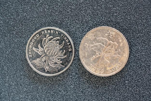 Closeup vista lateral traseira de 1 yuan chinês e moedas de 1 dólar hong kong em fundo escuro Foto Premium