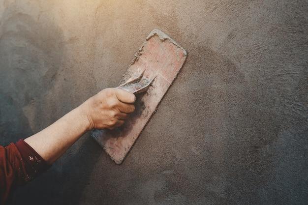 Closup mão dos trabalhadores de reboco na parede ao ar livre no canteiro de obras Foto Premium