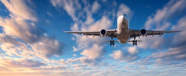 Cloudscape com avião de passageiro branco voando Foto Premium