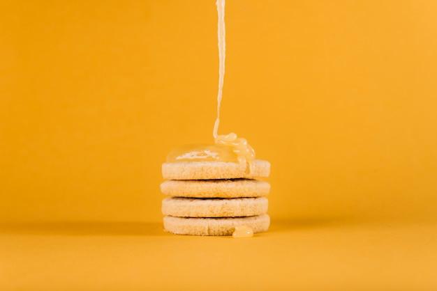 Coalho de limão, pingando em cookies empilhados na superfície amarela Foto gratuita