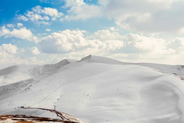 Cobertas de neve belas montanhas com céu azul Foto gratuita