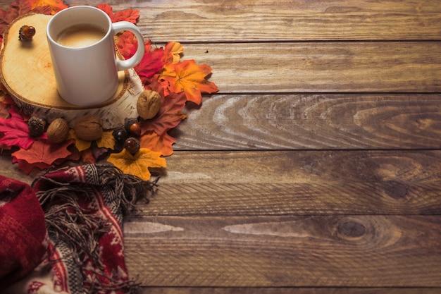 Cobertor e café perto de folhas e nozes Foto gratuita