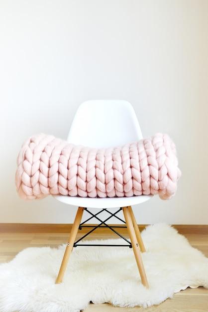 Cobertor xadrez rosa gigante de lã de malha no branco de madeira cadeira de fezes estilo escandinavo casa Foto Premium