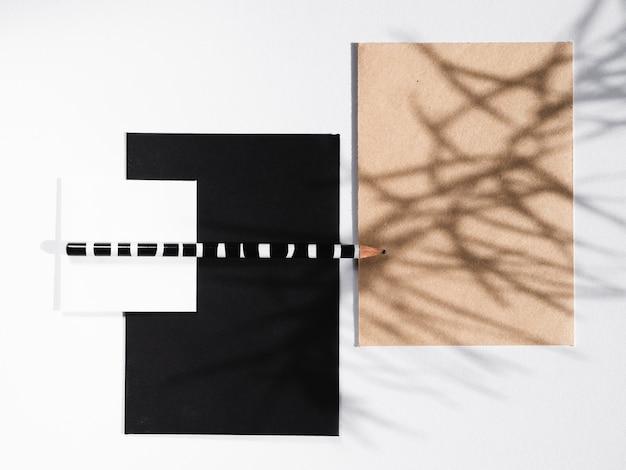 Cobertores preto e branco com um lápis listrado e um cobertor bege com uma sombra de galho Foto gratuita