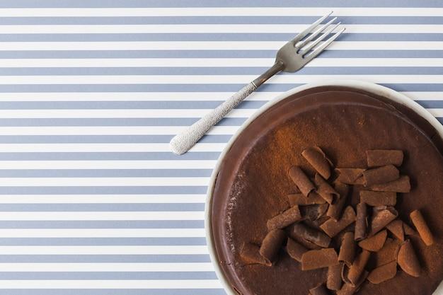 Coberturas de pedaços de chocolate no bolo assado sobre o fundo de listras Foto gratuita