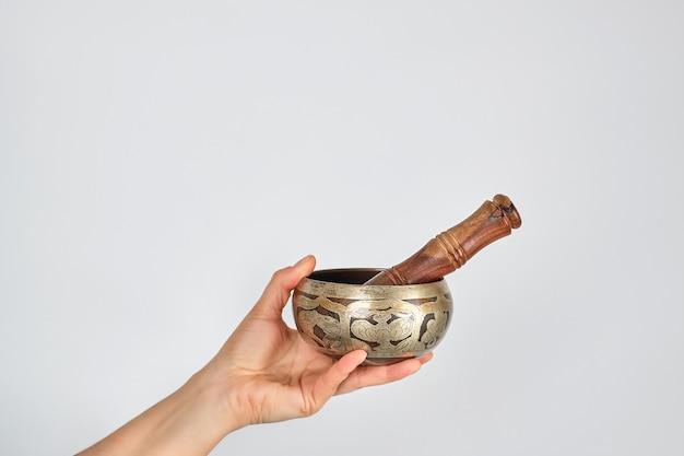 Cobre cantando tigela e vara de madeira na mão feminina Foto Premium