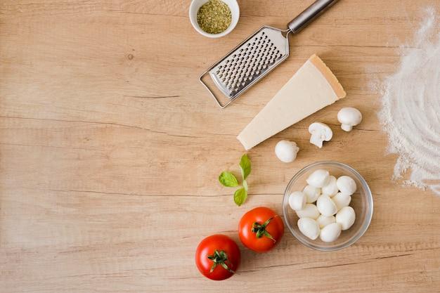 Cobrindo os ingredientes para pizza com ralador de metal no fundo de madeira Foto gratuita