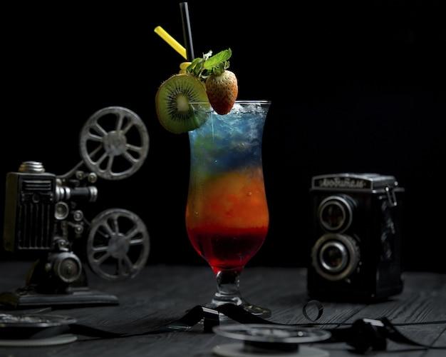 Cocktail arco-íris com kiwi e morangos no topo Foto gratuita