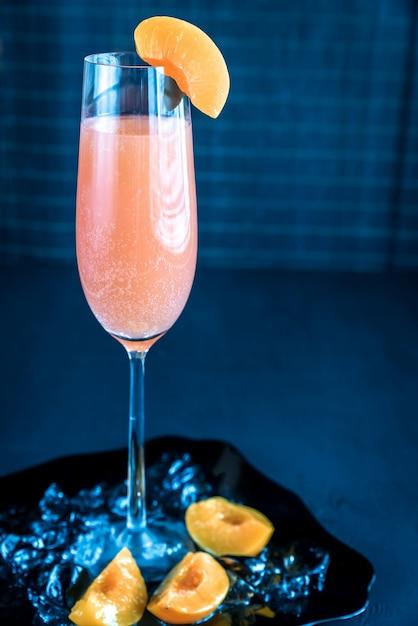 Cocktail bellini em flauta decorada com pêssego Foto Premium