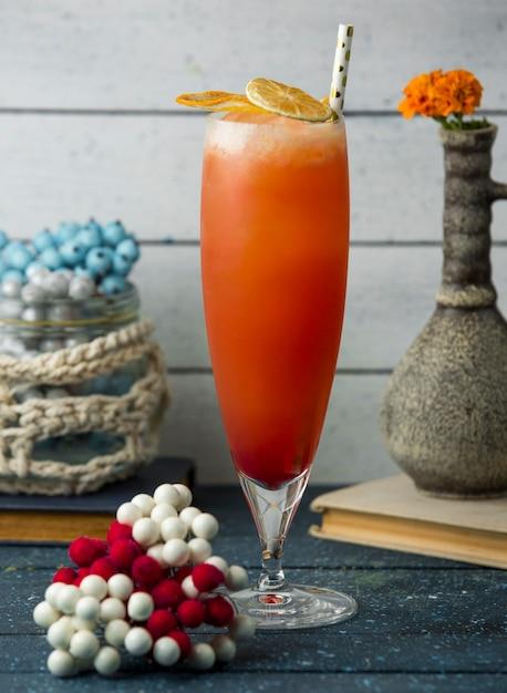 Cocktail cítrico, guarnecido com fatias de limão e laranja secas Foto gratuita