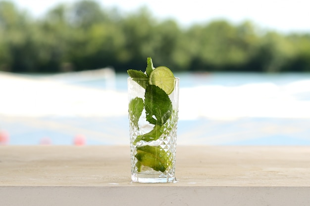 Cocktail com hortelã e gelo em um copo de vidro. com decoração de flores e frutas Foto Premium