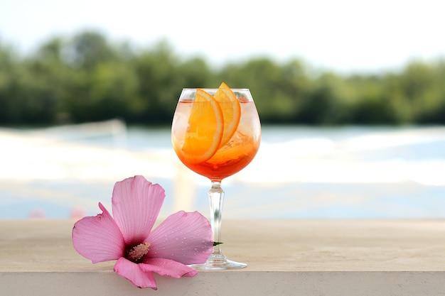 Cocktail com laranja e gelo em um copo de vidro. com decoração de flores Foto Premium