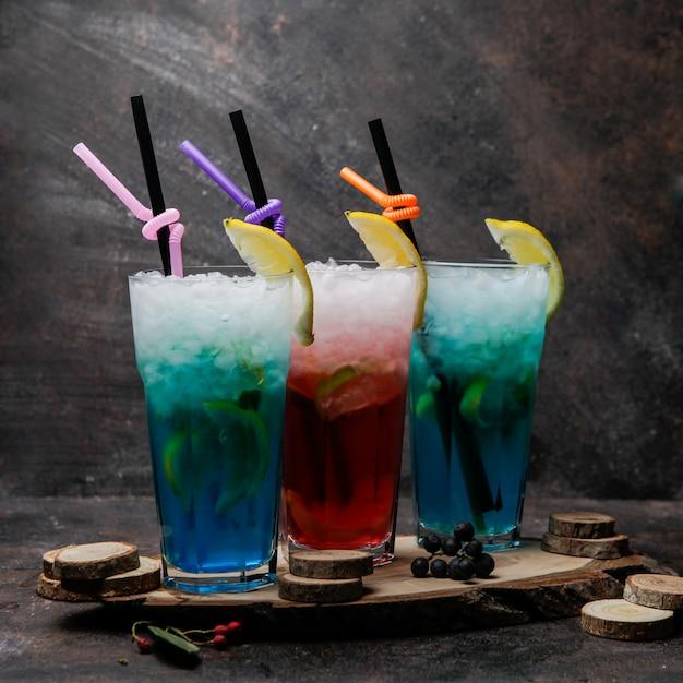 Cocktail de álcool close-up copos de lagoa azul cocktail decorado com limão e copo de coquetel com uísque em um carrinho de madeira Foto gratuita