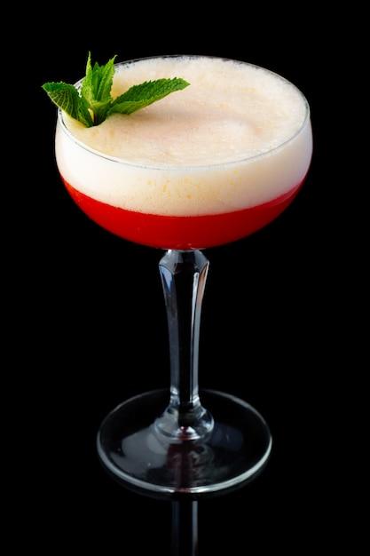 Cocktail de álcool vermelho com hortelã isolada no fundo preto Foto Premium
