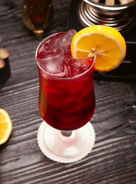 Cocktail de álcool vermelho no copo com cubos de gelo e fatia de limão Foto gratuita