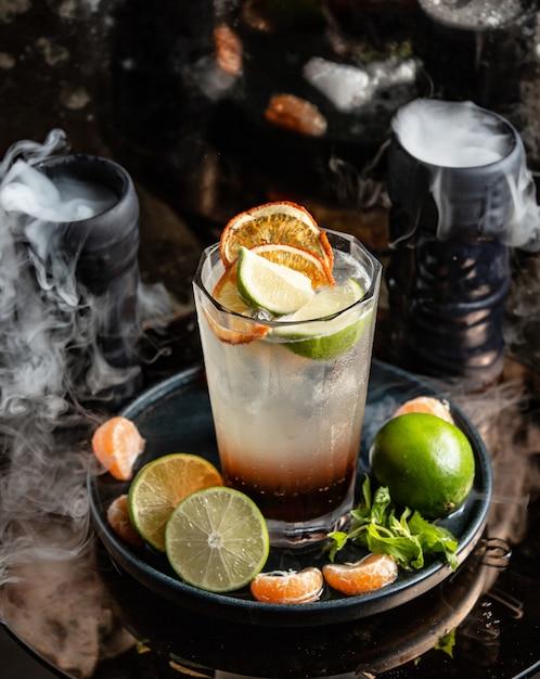 Cocktail de citrinos com fatias de laranja e limão em torno de copos fumados Foto gratuita