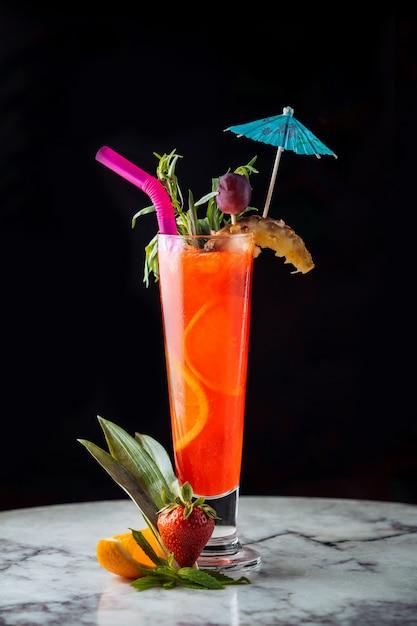 Cocktail de suco de laranja com acessórios coloridos. Foto gratuita