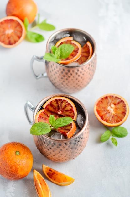 Cocktail do álcool da mula de moscou da laranja pigmentada com as folhas de hortelã fresca e gelo nas canecas de cobre em um fundo concreto cinzento. Foto Premium