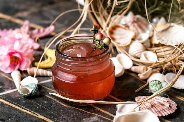 Cocktail em jarra colocada em torno de conchas e estrelas do mar Foto gratuita