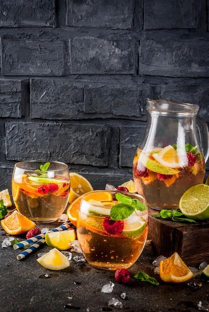 Cocktail frio de verão, sangria de frutas e bagas brancas com maçã, limão, laranja e framboesa Foto Premium