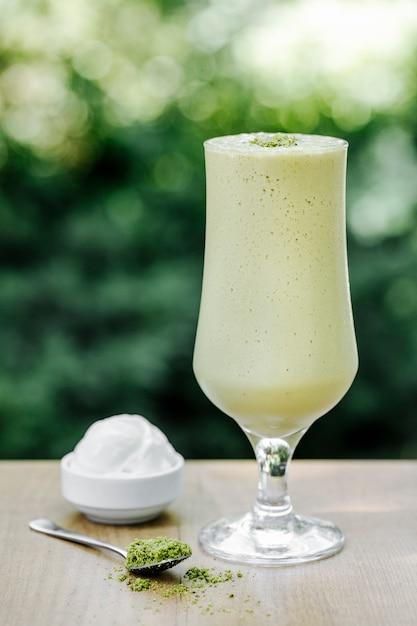Cocktail leitoso verde com bola de sorvete no terraço. Foto gratuita