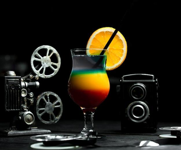 Cocktail multicolorido com gelo na mesa Foto gratuita