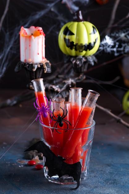 Cocktail sangrento em tubos de vidro para festa de halloween. Foto Premium