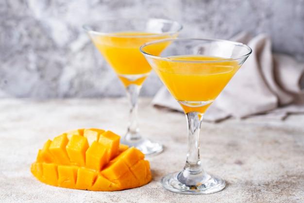 Cocktail tropical com manga em fundo claro Foto Premium
