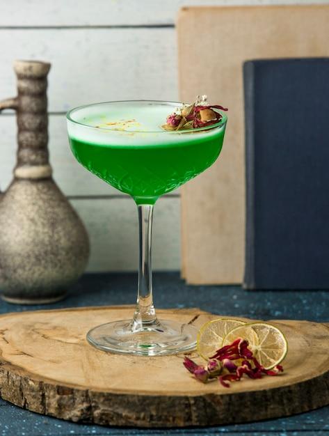 Cocktail verde decorado com botões de rosa secos em vidro cristal Foto gratuita