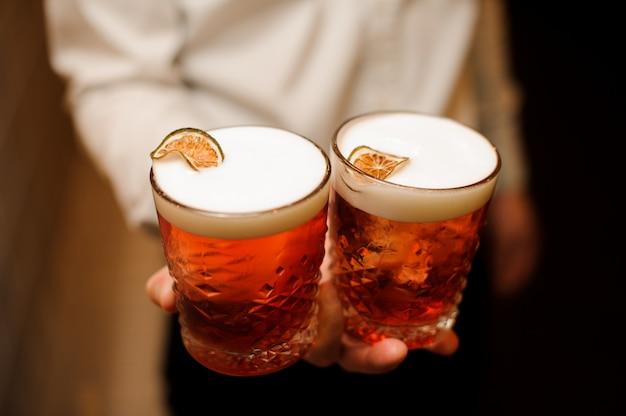 Cocktail vermelho com espuma doce e limão fresco nas mãos de barmen Foto Premium