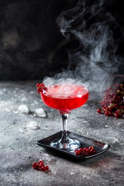 Cocktail vermelho com vapor de gelo. Foto Premium