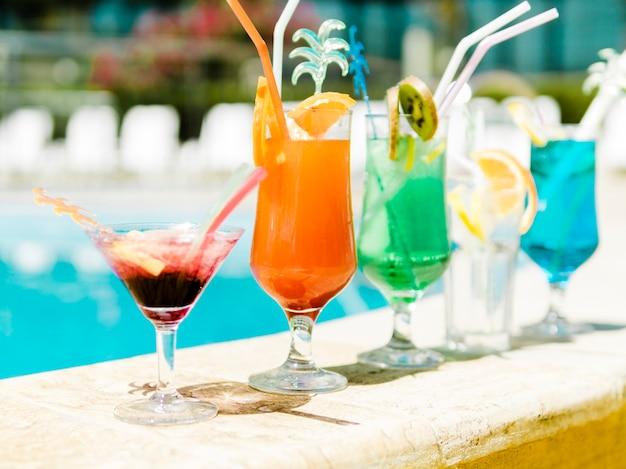 Cocktails coloridos à beira da piscina Foto gratuita