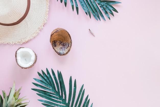Coco com folhas de palmeira e chapéu de palha Foto gratuita