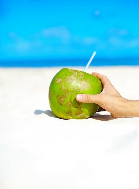 Coco com mão na praia branca Foto gratuita