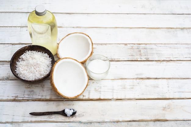 Coco com óleo de coco na garrafa no fundo da mesa branca Foto Premium