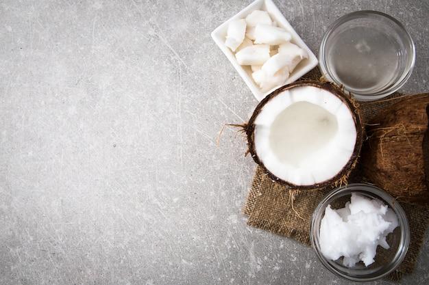 Coco com óleo de coco no pote em fundo de madeira Foto Premium