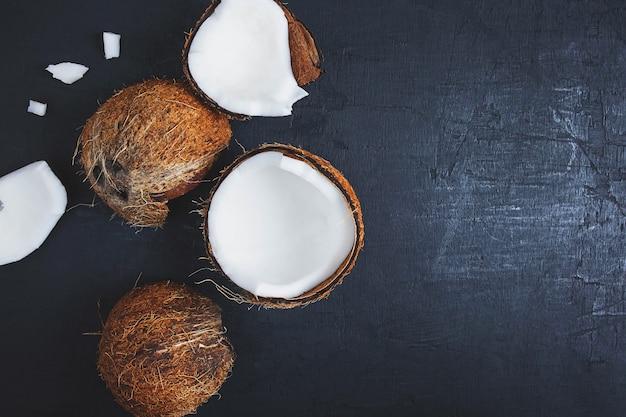 Coco cortado ao meio em um fundo preto Foto Premium