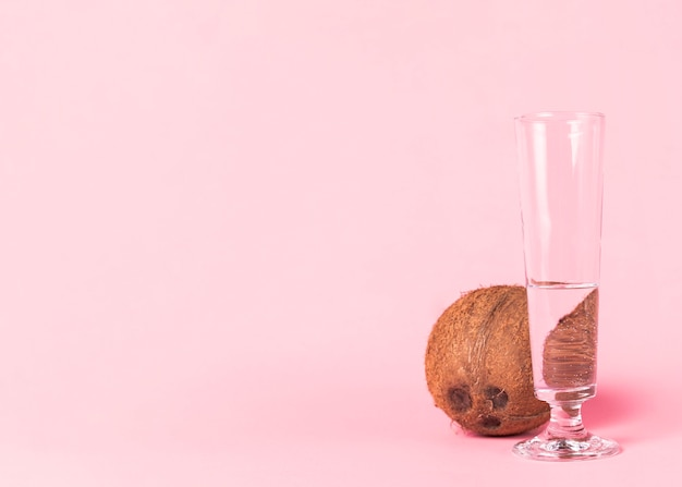 Coco e copo de água no fundo rosa Foto gratuita