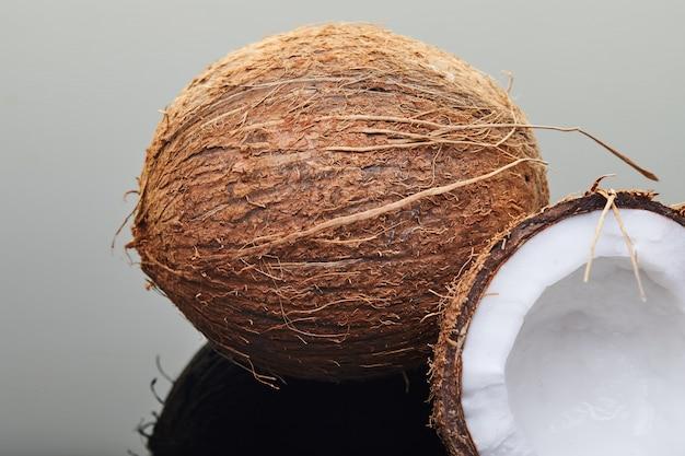 Coco inteiro e meio fresco em cinza com reflexão Foto Premium