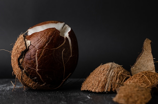 Coco quebrado cru no escuro Foto Premium