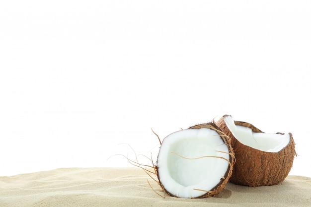 Cocos na areia clara do mar, isolada no fundo branco. férias de verão Foto Premium